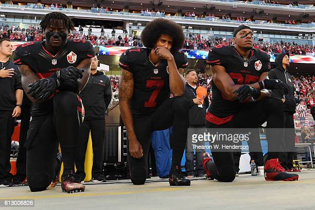 Eli Harold, Colin Kaepernick, and Eric Reid of the San Francisco 49ers kneel in protest during the national anthem prior to their NFL game against...