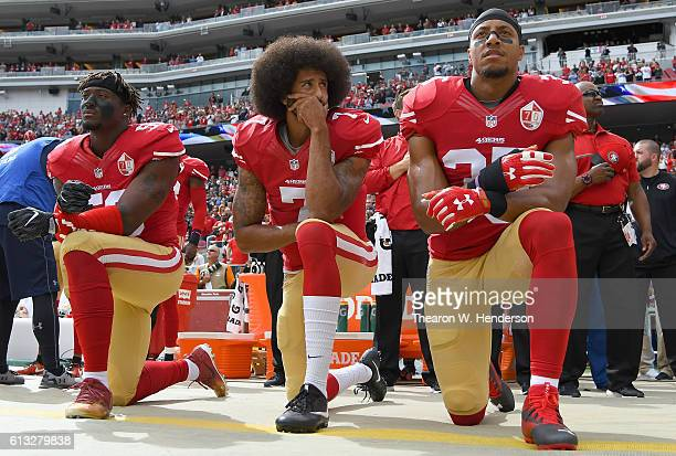 Eli Harold Colin Kaepernick and Eric Reid of the San Francisco 49ers kneel on the sideline during the National Anthem prior to the game against the...