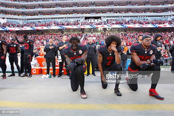 Eli Harold Colin Kaepernick and Eric Reid of the San Francisco 49ers kneel on the sideline during the anthem prior to the game against the Arizona...