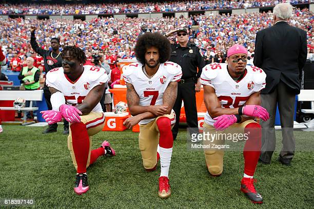 Eli Harold, Colin Kaepernick and Eric Reid of the San Francisco 49ers kneel in protest on the sideline, during the anthem, prior to the game against...