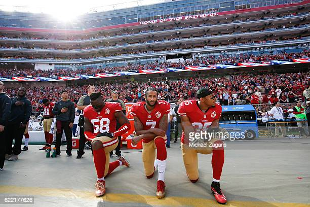 Eli Harold Colin Kaepernick and Eric Reid of the San Francisco 49ers kneel on the sideline during the anthem prior to the game against the New...