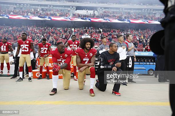 Eli Harold Colin Kaepernick and Eric Reid of the San Francisco 49ers kneel on the sideline during the anthem prior to the game against the New York...