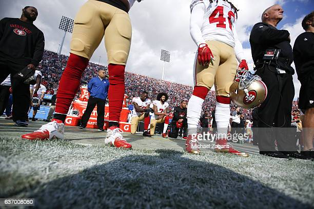 Eli Harold Colin Kaepernick and Eric Reid of the San Francisco 49ers kneel on the sideline during the anthem prior to the game against the Los...
