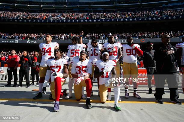 Eli Harold Eric Reid and Marquise Goodwin of the San Francisco 49ers kneel on the sideline during the anthem as teammates Solomon Thomas Reuben...