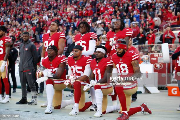 Eli Harold Eric Reid Marquise Goodwin and Louis Murphy of the San Francisco 49ers kneel on the sideline during the anthem as Solomon Thomas Reuben...