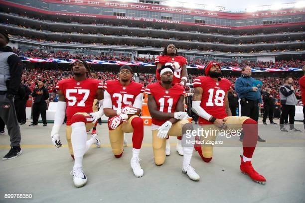 Eli Harold Eric Reid Marquise Goodwin and Louis Murphy of the San Francisco 49ers kneel on the sideline as Adrian Colbert stands with them in...
