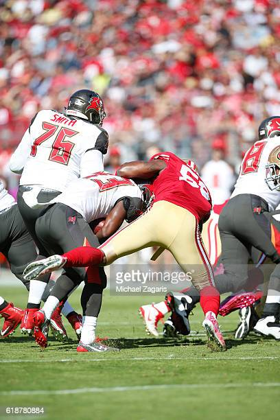 Eli Harold of the San Francisco 49ers tackles Peyton Barber of the Tampa Bay Buccaneers during the game at Levi Stadium on October 23 2016 in Santa...
