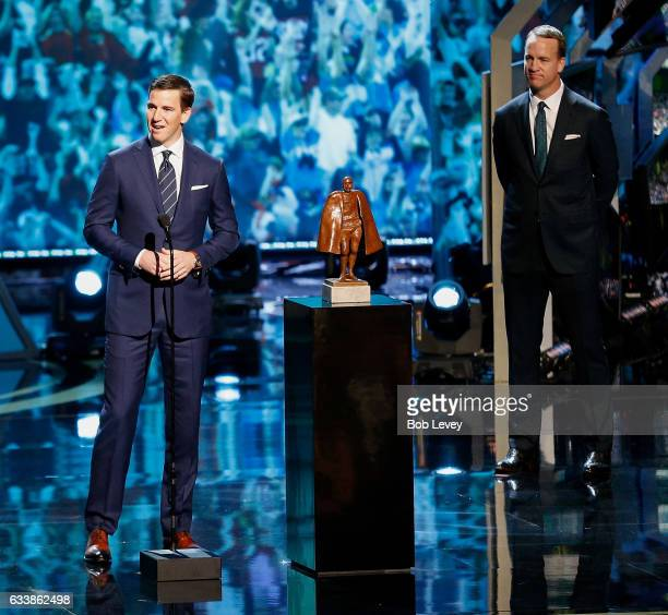 Eli Manning accepts the Walter Payton NFL Man of the Year presented by Nationwide as his brother Peyton Manning a former winner of the award looks on...