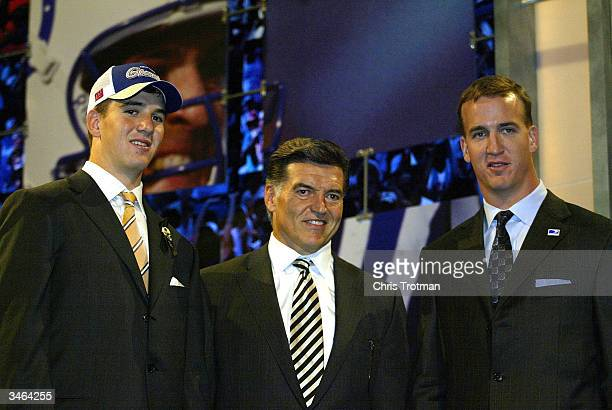 Eli Manning agent Tom Condon and brother Colts quarterback Peyton Manning pose during the 2004 NFL Draft on April 24 2004 at Madison Square Garden in...