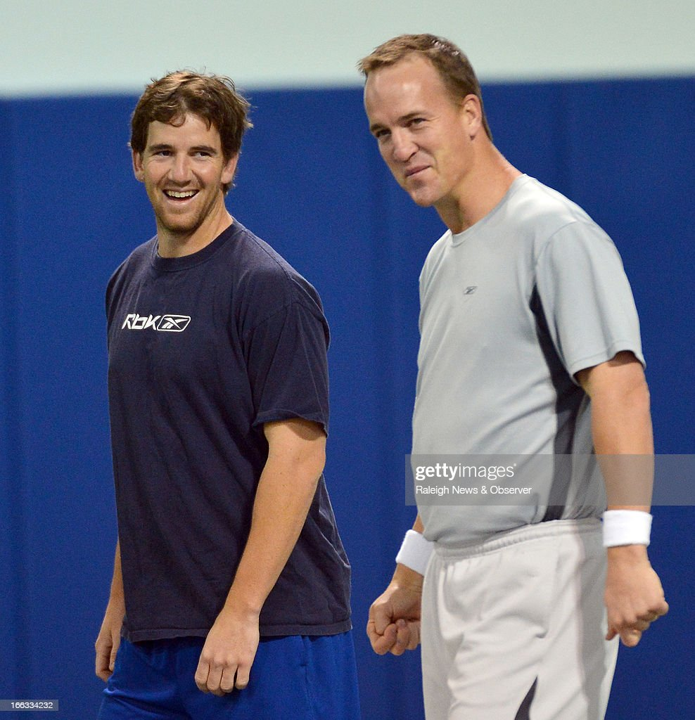 Eli Manning and his brother Peyton laugh as they run through warm up exercises at Duke's Pascal Field House in Durham, North Carolina, Thursday, April 11, 2013.
