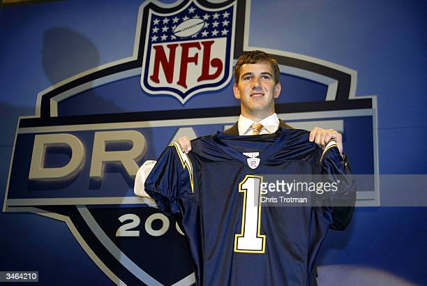 Eli Manning holding up a San Diego Chargers jersey was selected first pick overall by the Chargers then traded to the New York Giants for Philip...