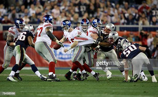 Eli Manning of the New York Giants breaks free from the grasp of Richard Seymour of the New England Patriots, Manning scrambled free to throw a 32...