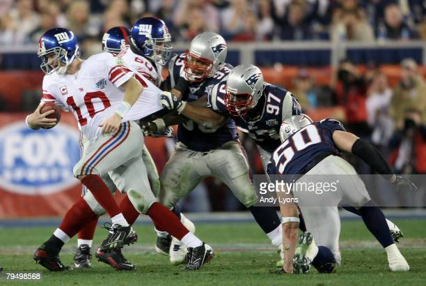 Eli Manning of the New York Giants breaks free from the grasp of Richard Seymour of the New England Patriots Manning scrambled free to throw a 32...