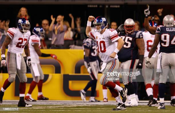 Eli Manning of the New York Giants celebrates after his first quarter touchdown pass to Victor Cruz against the New England Patriots during Super...