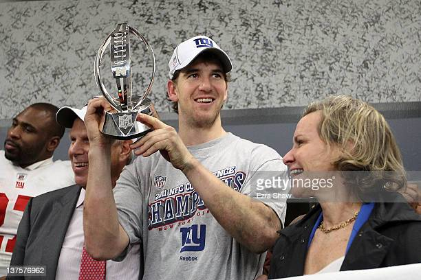 Eli Manning of the New York Giants celebrates in the locker room with the George Halas Trophy NFC Championship trophy after the GIants won 2017 in...