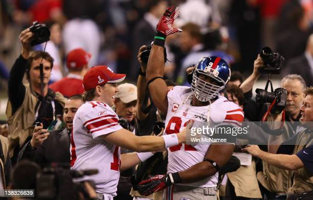 Eli Manning of the New York Giants celebrates with Justin Tuck after defeating the New England Patriots to win the Super Bowl XLVI at Lucas Oil...