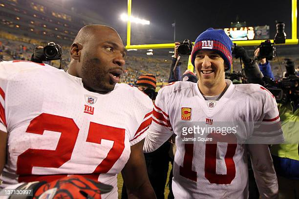 Eli Manning of the New York Giants celebrates with teammatee Brandon Jacobs after defeating the Green Bay Packers during their NFC Divisional playoff...