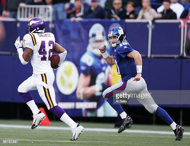 Eli Manning of the New York Giants chases Darren Sharper of the Minnesota Vikings on his way for a touchdown after intercepting Manning during their...