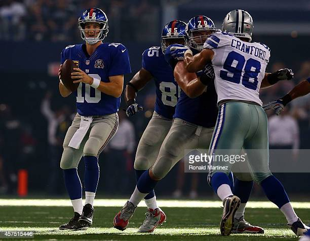 Eli Manning of the New York Giants drops back to pass as Tyrone Crawford of the Dallas Cowboys rushes in the second half at ATT Stadium on October 19...