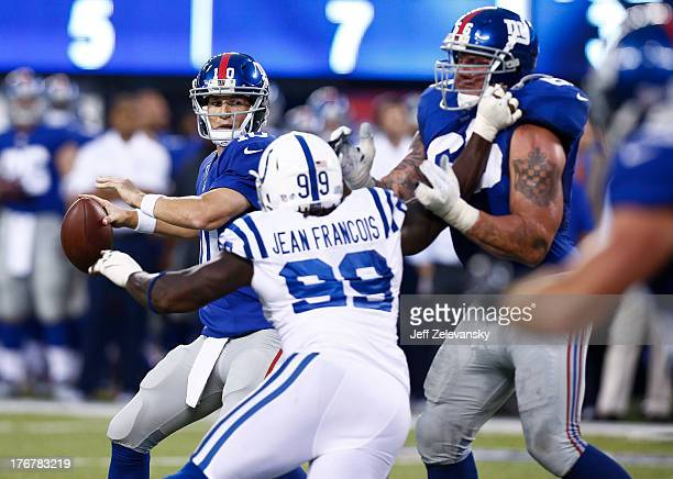 Eli Manning of the New York Giants eyes Ricky Jean Francois of the Indianapolis Colts during their preseason game at MetLife Stadium on August 18...