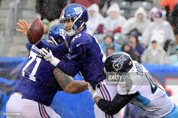 Eli Manning of the New York Giants fumbles the ball as he is wrapped up by Kamalei Correa of the Tennessee Titans during the second half at MetLife...