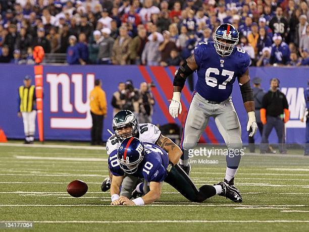 Eli Manning of the New York Giants fumbles the ball late in the game as he is taken down by Jason Babin of the Philadelphia Eagles on November 20...