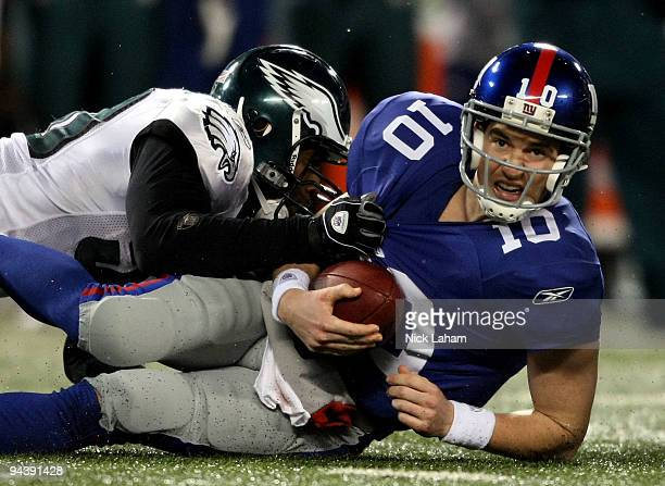 Eli Manning of the New York Giants gets sacked late in the game by Will Witherspoon of the Philadelphia Eagles at Giants Stadium on December 13 2009...