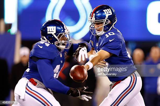 Eli Manning of the New York Giants hands the ball off to Andre Williams against the Indianapolis Colts in the first quarter during their game at...