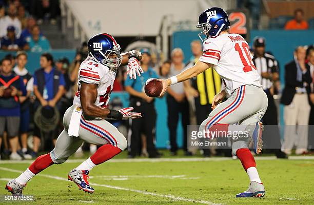 Eli Manning of the New York Giants hands the ball off to Andre Williams during the first half of the game against the Miami Dolphins at Sun Life...