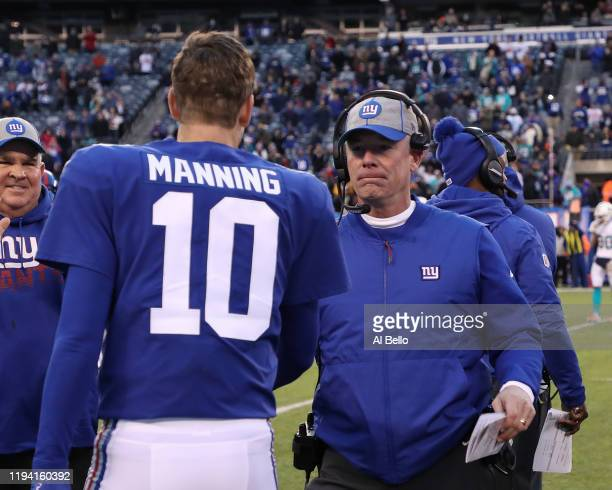 Eli Manning of the New York Giants hugs head coach Pat Shurmur of the New York Giants in the final seconds of their 3113 win against the Miami...