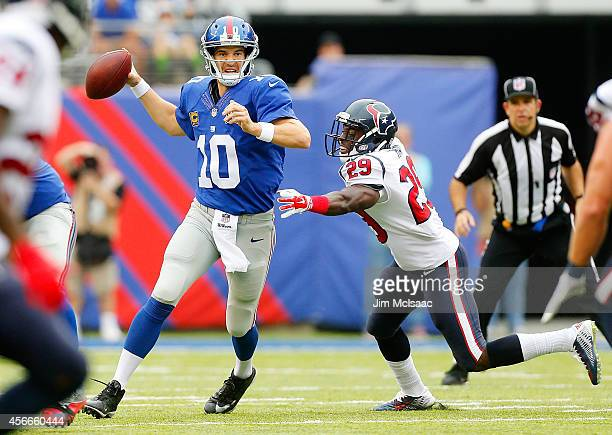 Eli Manning of the New York Giants in action against Andre Hal of the Houston Texans on September 21, 2014 at MetLife Stadium in East Rutherford, New...