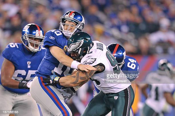 Eli Manning of the New York Giants is hit by Jason Babin of the Philadelphia Eagles at MetLife Stadium on November 20 2011 in East Rutherford New...