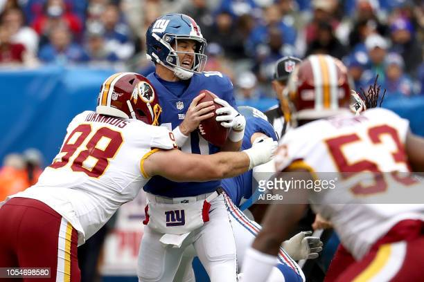 Eli Manning of the New York Giants is hit by Matthew Ioannidis of the Washington Redskins during the first quarter at MetLife Stadium on October 28,...
