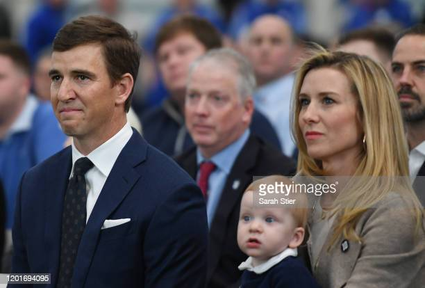 Eli Manning of the New York Giants looks on with his wife, Abby, and son, Charles, during a press conference to announce his retirement on January...