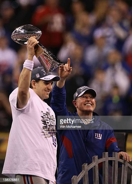 Eli Manning of the New York Giants poses with the Vince Lombardi Trophy and his head coach Tom Coughlin after the Giants defeated the Patriots by a...