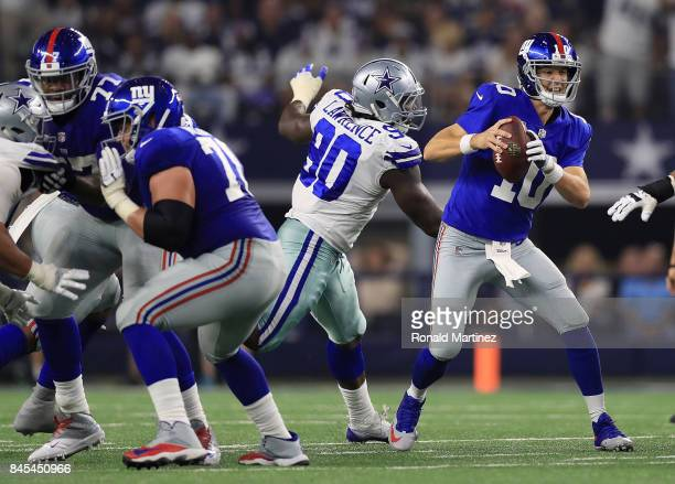 Eli Manning of the New York Giants scrambles away from DeMarcus Lawrence of the Dallas Cowboys in the second half of a game at ATT Stadium on...