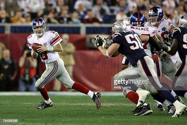 Eli Manning of the New York Giants scrambles away from th New England Patriots defense to throw a 32 yard pass to David Tyree of the Giants during...