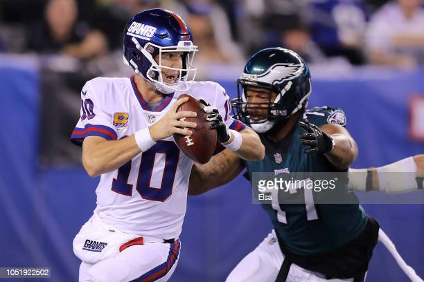 Eli Manning of the New York Giants scrambles before fumbling the ball from a hit by Michael Bennett of the Philadelphia Eagles during the first...