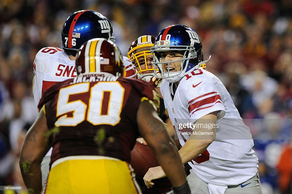 Eli Manning #10 of the New York Giants scrambles with the ball before he is sacked by the Washington Redskins in the second half of a game at FedExField on December 3, 2012 in Landover, Maryland.