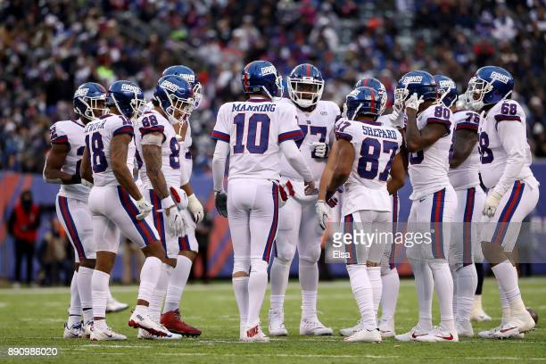 Eli Manning of the New York Giants talks with his teammates in a huddle against the Dallas Cowboys during the second half in the game at MetLife...