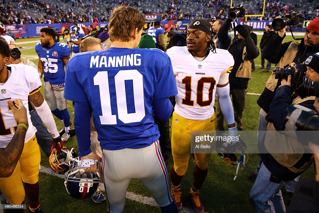 Eli Manning #10 of the New York Giants talks with Robert Griffin III #10 of the Washington Redskins after their game at MetLife Stadium on December 14, 2014 in East Rutherford, New Jersey. The New York Giants defeated the Washington Redskins 24 to 13.