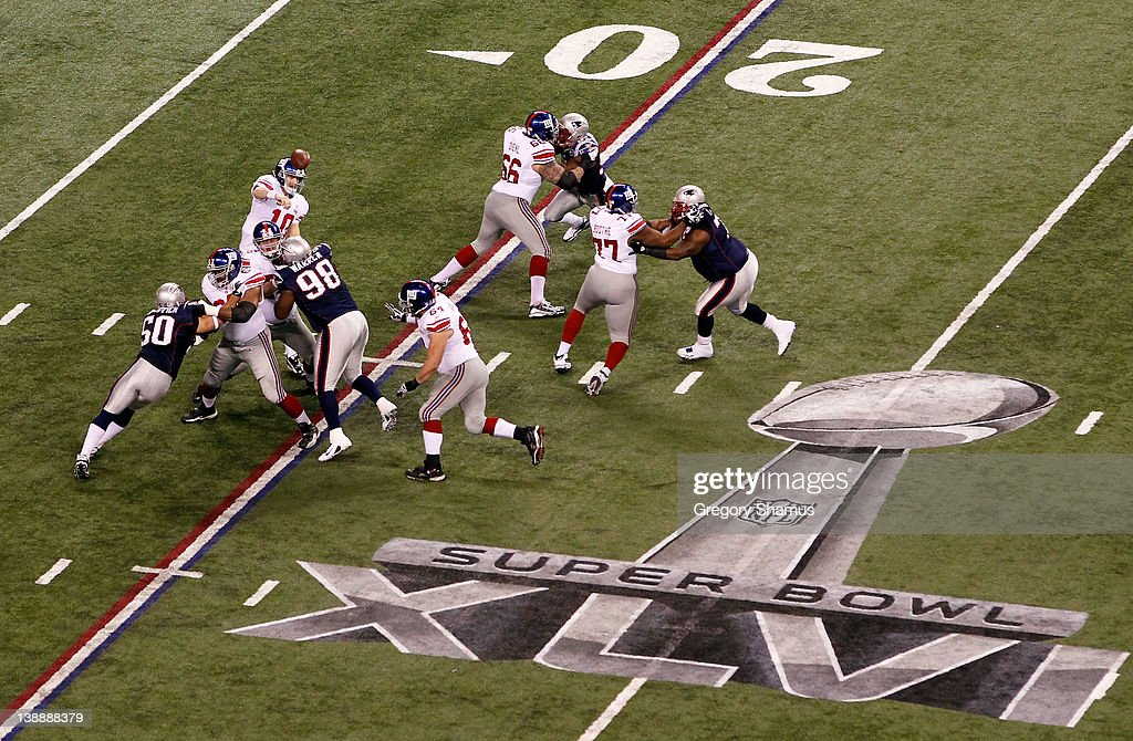 Eli Manning #10 of the New York Giants throws a pass behind the offensive line against the New England Patriots during Super Bowl XLVI at Lucas Oil Stadium on February 5, 2012 in Indianapolis, Indiana. The Giants won 21-17.