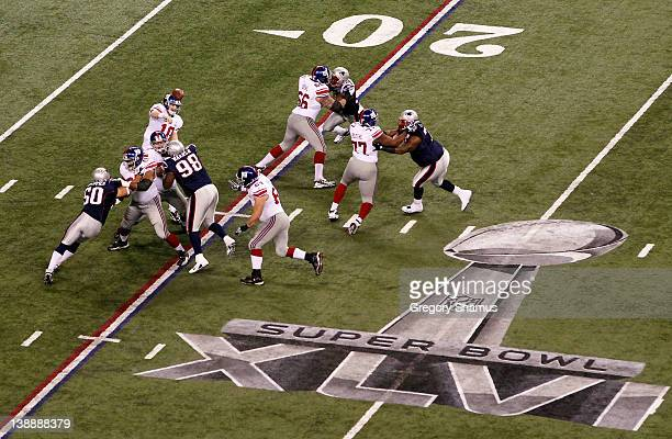 Eli Manning of the New York Giants throws a pass behind the offensive line against the New England Patriots during Super Bowl XLVI at Lucas Oil...