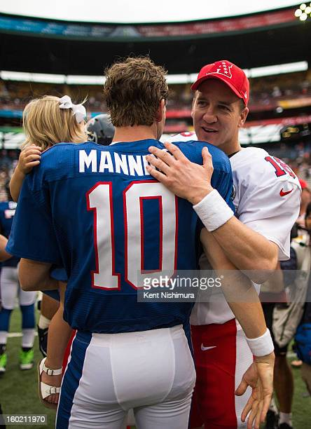 Eli Manning of the NFC's New York Giants greets his brother Peyton Manning of the AFC's Denver Broncos after the conclusion of the 2013 AFCNFC Pro...