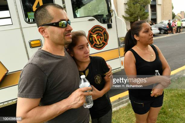 Eli Mendoza left hugs his daughter Maria as they and his wife Yolanda De Santiagoright watch as firefighters search their apartment for their 6...