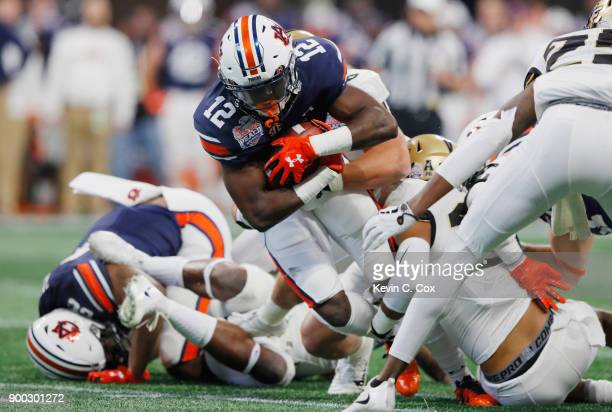 Eli Stove of the Auburn Tigers carries the ball in the first half against the UCF Knights during the ChickfilA Peach Bowl at MercedesBenz Stadium on...