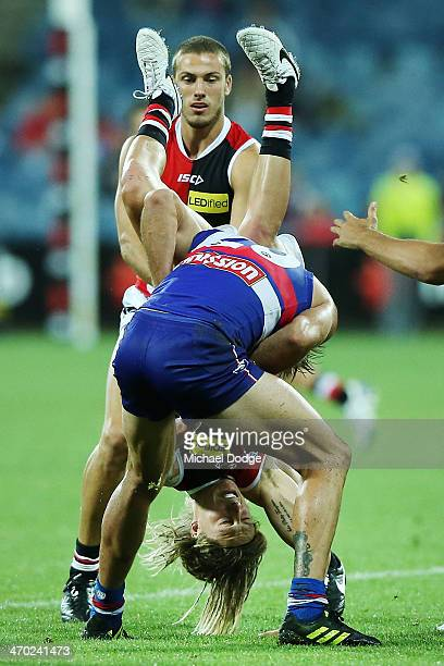 Eli Templeton of the Saints tackles and tumbles over Koby Stevens of the Bulldogs during the round two AFL NAB Challenge Cup match between the...