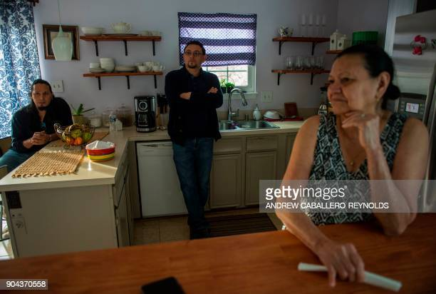 Eli Villalta a Salvadorian immigrant affected by the US governments announcement to end 'temporary protected status' rests on a counter near members...