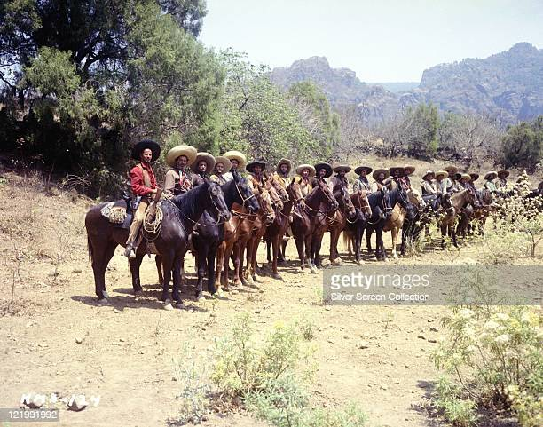 Eli Wallach, US actor, on horseback in the foreground at the head of a long line of Mexican bandits on horseback in a publicity still issued for the...
