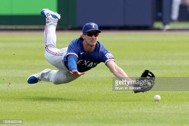 Eli White of the Texas Rangers attempts to catch a fly ball hit by George Springer of the Toronto Blue Jays during the first inning in game two of a...